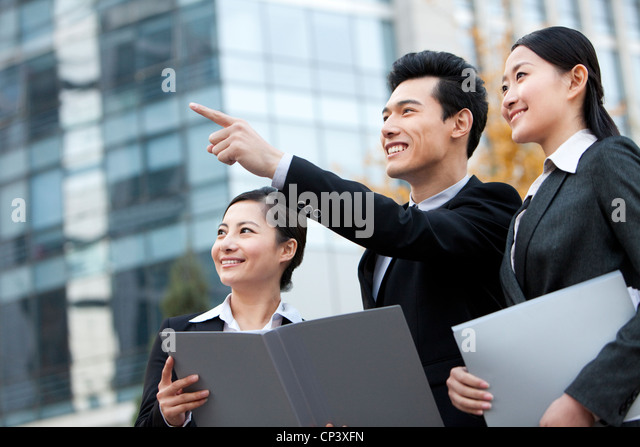A team of businesspeople outside office buildings pointing and planning - Stock Image