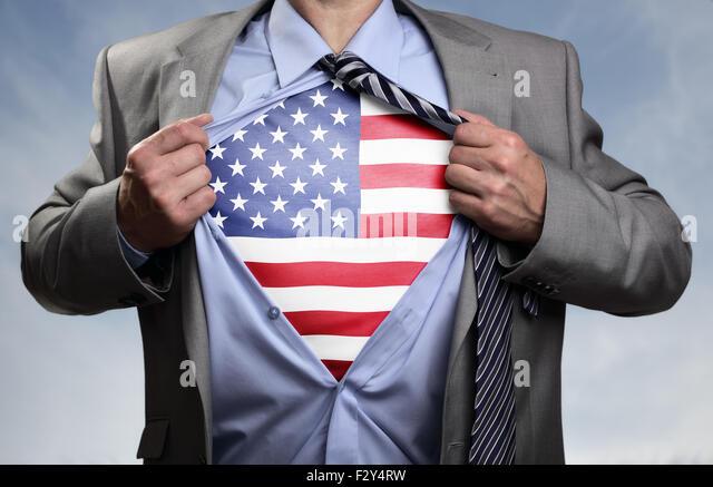 Superhero businessman revealing American flag - Stock Image