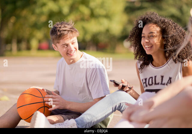 Group of young adult basketball players sitting chatting - Stock-Bilder