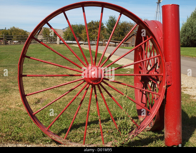 Entry gate made from old red tractor wheels at O'Keefe Ranch in Vernon, British Columbia, Canada - Stock Image