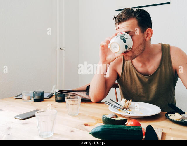Man Drinking Coffee By Messy Table - Stock Image