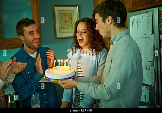 Friends celebrating birthday at home - Stock Image