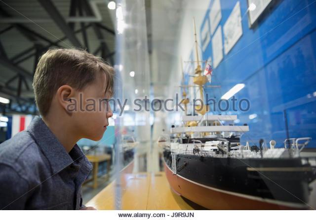Curious boy viewing Naval ship exhibit in war museum - Stock-Bilder