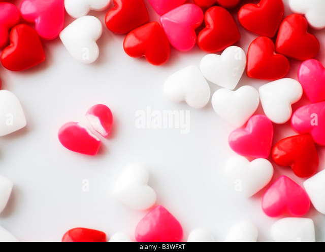 Heart-shaped candies, one broken - Stock Image