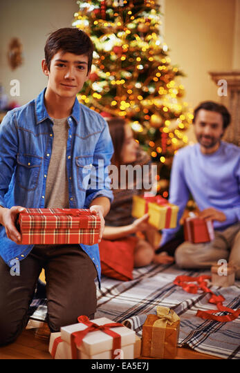 Youthful guy with giftboxes looking at camera with his parents on background - Stock Image