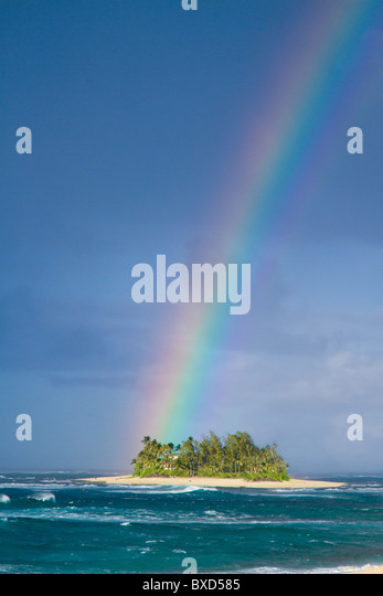 A brilliantly colored rainbow falling over a small desert island. - Stock Image