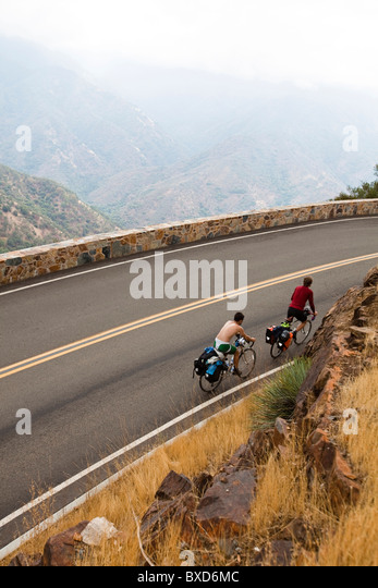 Two male cyclists climb up The Generals Highway while riding through Sequoia National Park, California. - Stock Image