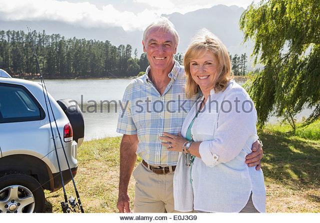 Senior Couple Enjoying Fishing Trip By Lake - Stock Image
