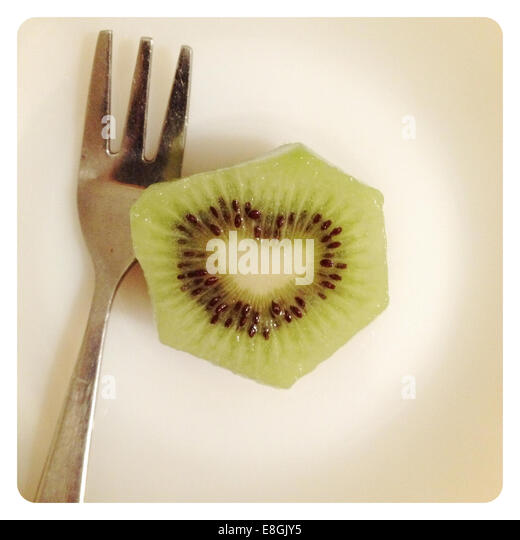 Kiwi fruit with heart shape seeds and fork - Stock Image