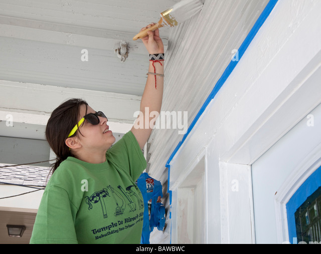 Volunteer paints house damaged by Hurricane Katrina in New Orleans - Stock Image