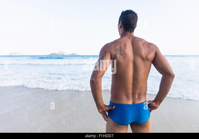 Mid adult man wearing swimming trunks, looking out to sea, rear view - Stock Image