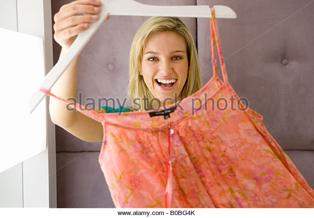 Young woman holding up dress on hanger, smiling, portrait - Stock Image