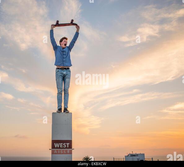 Portrait of young man standing on pillar holding skateboard above head - Stock-Bilder