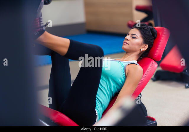 Portrait of a sports woman workout on exercises machine at fitness gym - Stock-Bilder