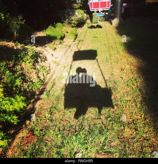 Shadow of overhead cable car in field - Stock Image