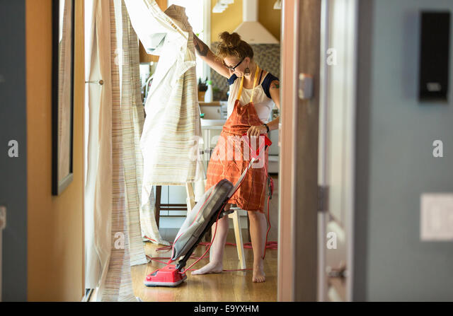 Young woman vacuuming with green cleaning products - Stock-Bilder
