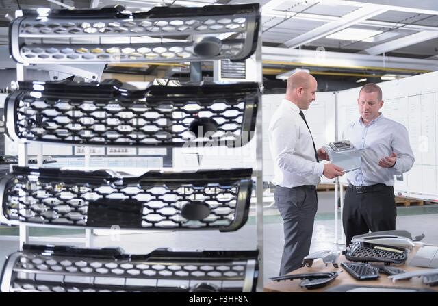 Managers inspecting automotive parts in spray paint factory - Stock Image