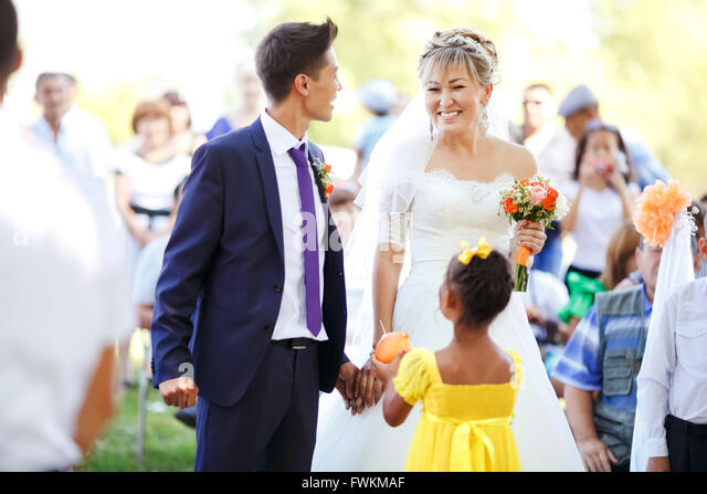 Happy emotional bride during wedding ceremony among guests outdoors. - Stock Image