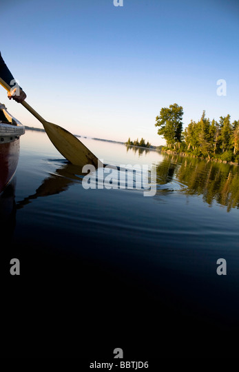 Canoe paddle dipped in tranquil lake - Stock Image