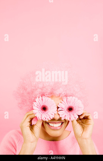 Woman wearing pink wig and holding flowers over eyes - Stock Image