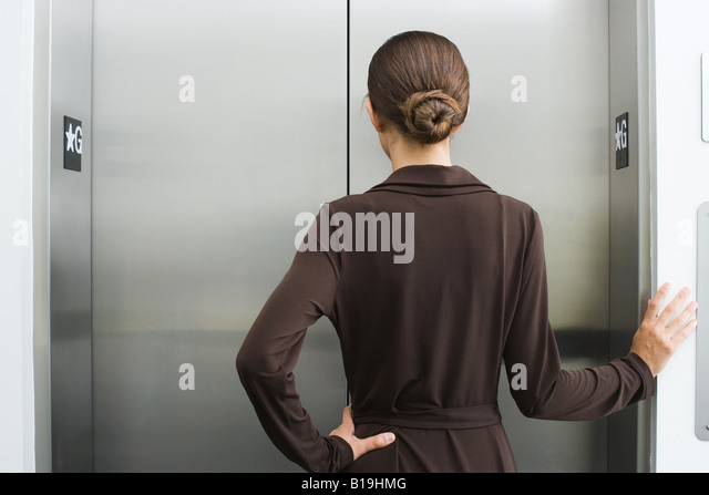 Well-dressed female waiting for elevator, rear view - Stock-Bilder