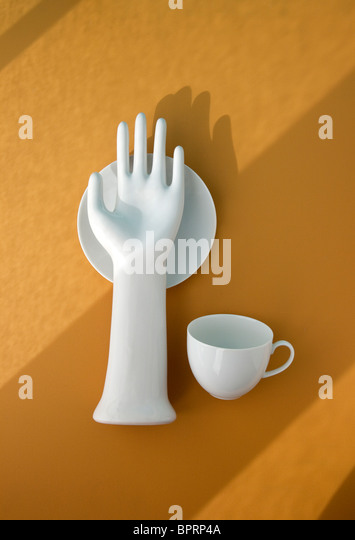white porcelain hand with cup and saucer on yellow with shadows - Stock-Bilder