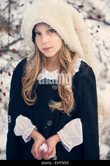 Sad looking girl holding snow in the shape of a heart - Stock Image