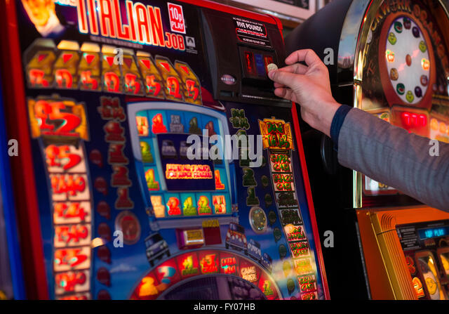 a man's hand putting money into a fruit machine gambling - Stock Image