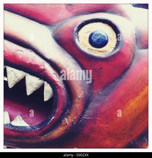 A close up view of the face of a handmade wooden monster - Stock Image