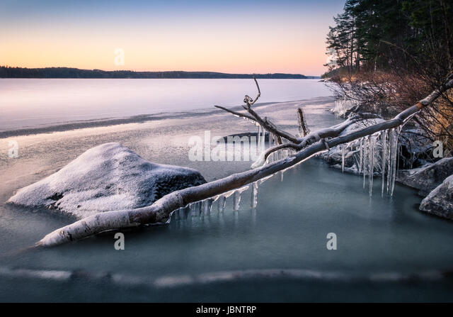 Scenic landscape with icicles and lake at the winter evening - Stock Image