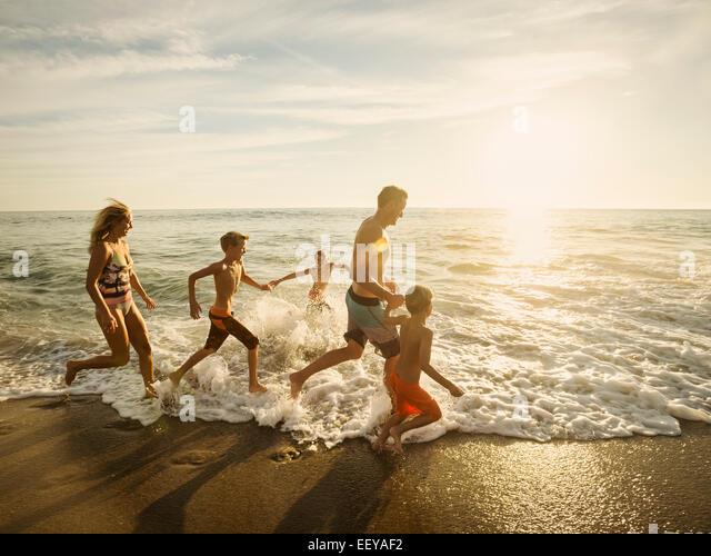 USA, California, Laguna Beach, Family with three children (6-7, 10-11, 14-15) running on beach - Stock-Bilder