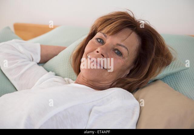 Portrait of senior woman lying on bed and smiling, Munich, Bavaria, Germany - Stock-Bilder