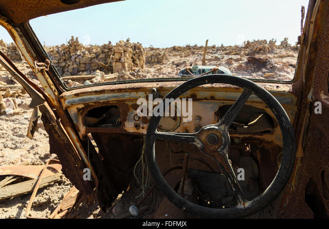 An ancient Fiat car slowly rots at an abandoned mineral extraction plant - Stock Image