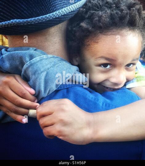 A little boy enjoys a hug. - Stock Image