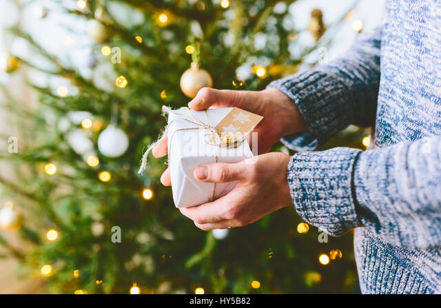 Finland, Man holding christmas gift against christmas tree - Stock Image
