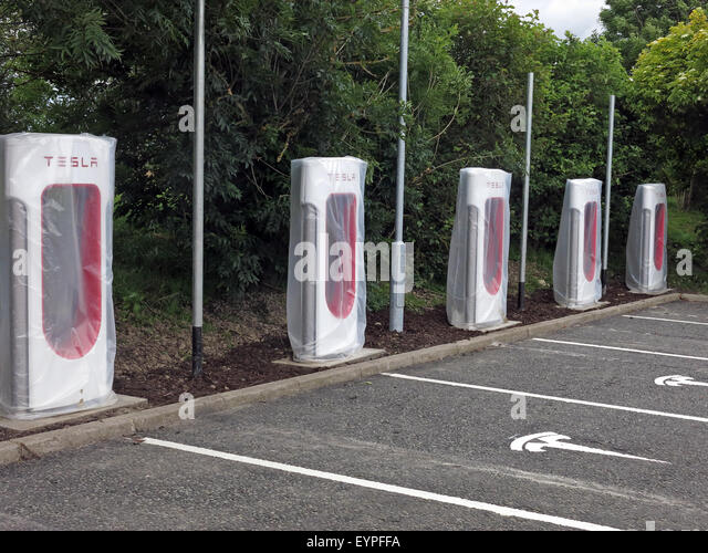 Tesla charging points being implemented on a motorway service area in the UK - Stock Image