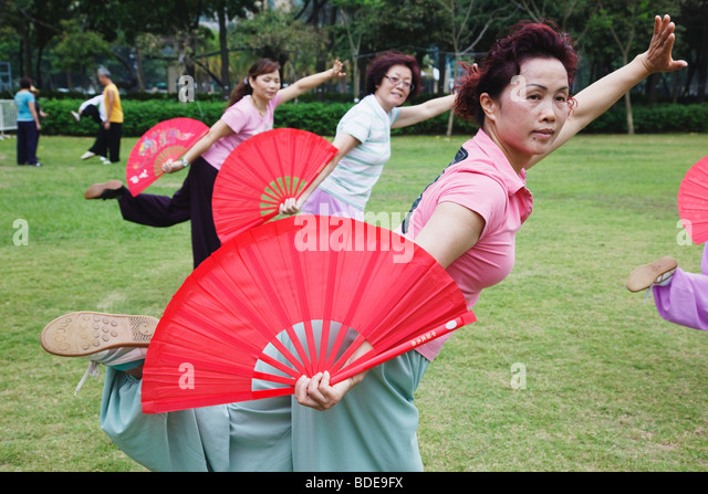 Group of women exercising with fans Victoria Park Hong Kong China. - Stock Image