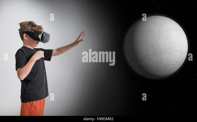 Young boy wearing virtual reality headset, reaching out to touch planet, digital composite - Stock-Bilder