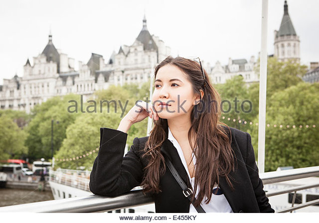 Young female tourist gazing from Golden Jubilee footbridge, London, UK - Stock Image