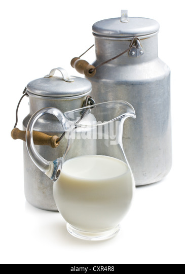 milk in a glass pitcher on white background - Stock Image