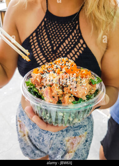 Mid section of young woman eating poke bowl at Hermosa Beach, California, USA - Stock-Bilder