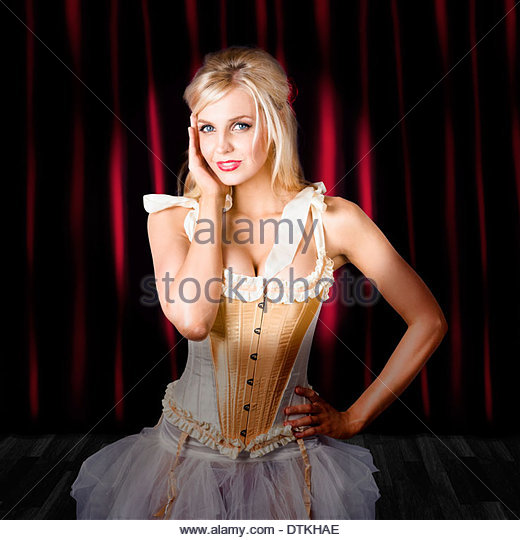Glamorous dancing woman in burlesque attire posing on red curtain stage in spot light. Act of dance - Stock Image