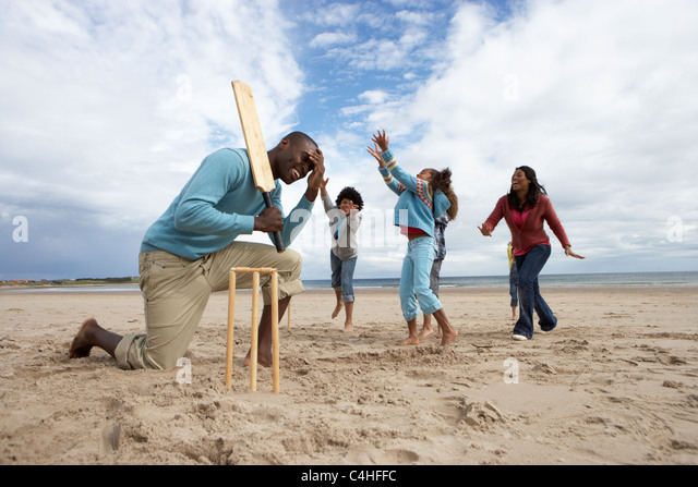 Family playing cricket on beach - Stock Image