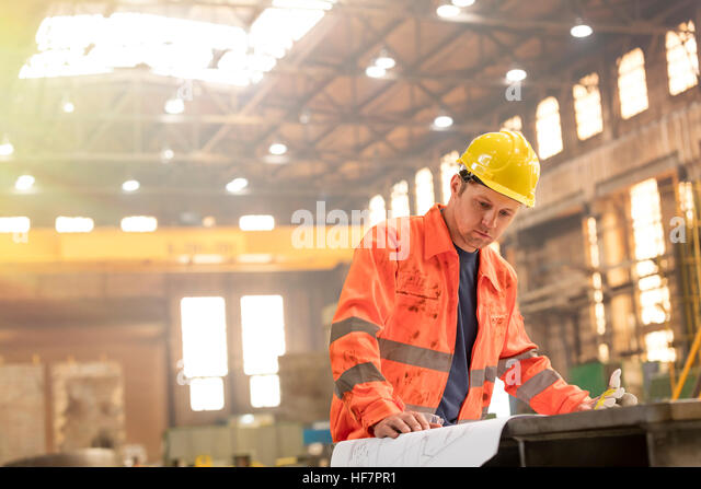 Engineer reviewing blueprints in steel factory - Stock Image