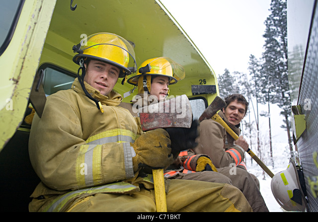three firefighters with axes sitting in the back of a fire truck - Stock Image