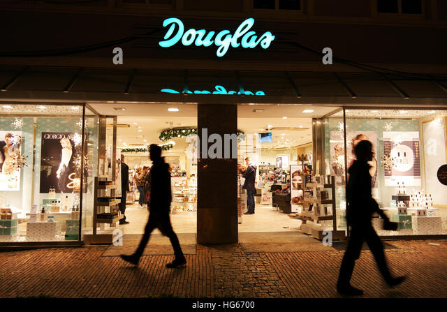 Silhouette of man as he passes a Douglas store by night. - Stock Image