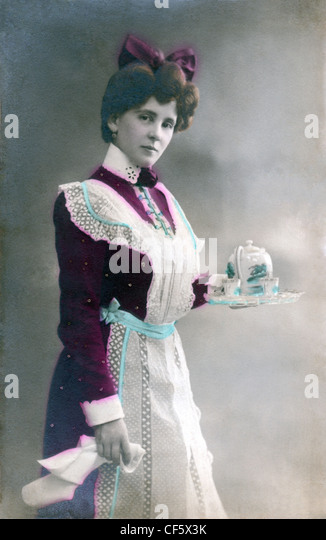 A maid dressed in her uniform and apron serving tea, circa 1910. - Stock Image
