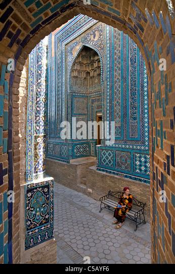 Uzbeki woman sitting on bench at Shahr i Zindah, Samarkand, Uzbekistan - Stock-Bilder