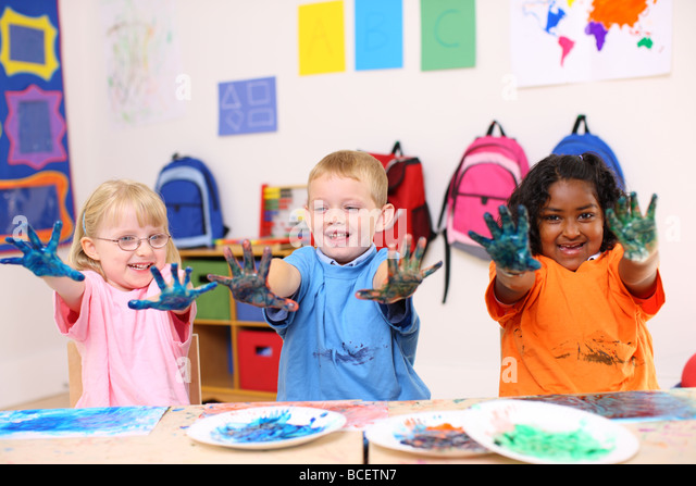 Three preschool kids with hands covered in paint - Stock Image