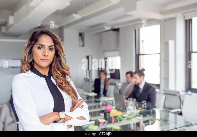 Confident businesswoman standing with arms crossed against colleagues at board room - Stock-Bilder